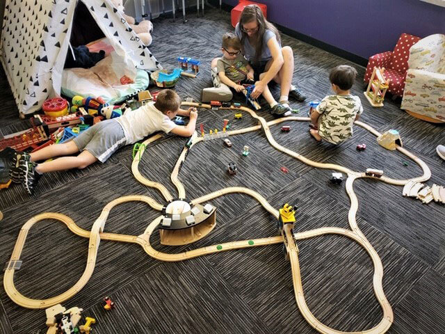 therapist and three children playing with a wooden train set